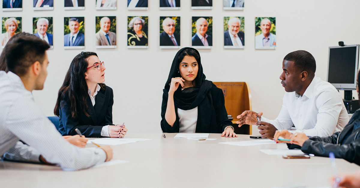 four people sitting at a round table having a conversation