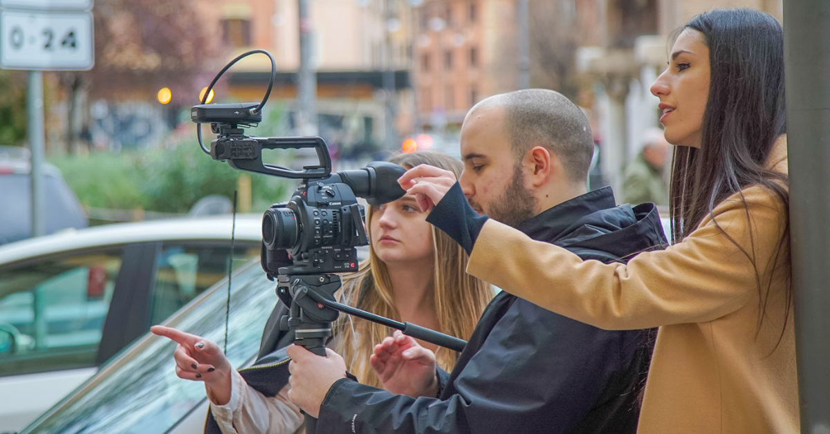 Three students operating a filming camera all facing the left hand side of the image
