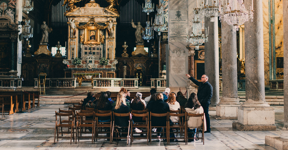 Students sitting in a church as professor explains the surroundings