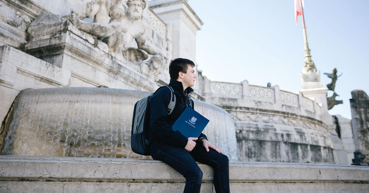 Boy sits in front of a fountain at Piazza Venezia