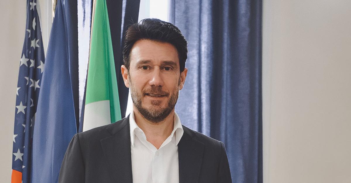 Uomo in posa davanti alle bandiere di Italia e Stati Uniti