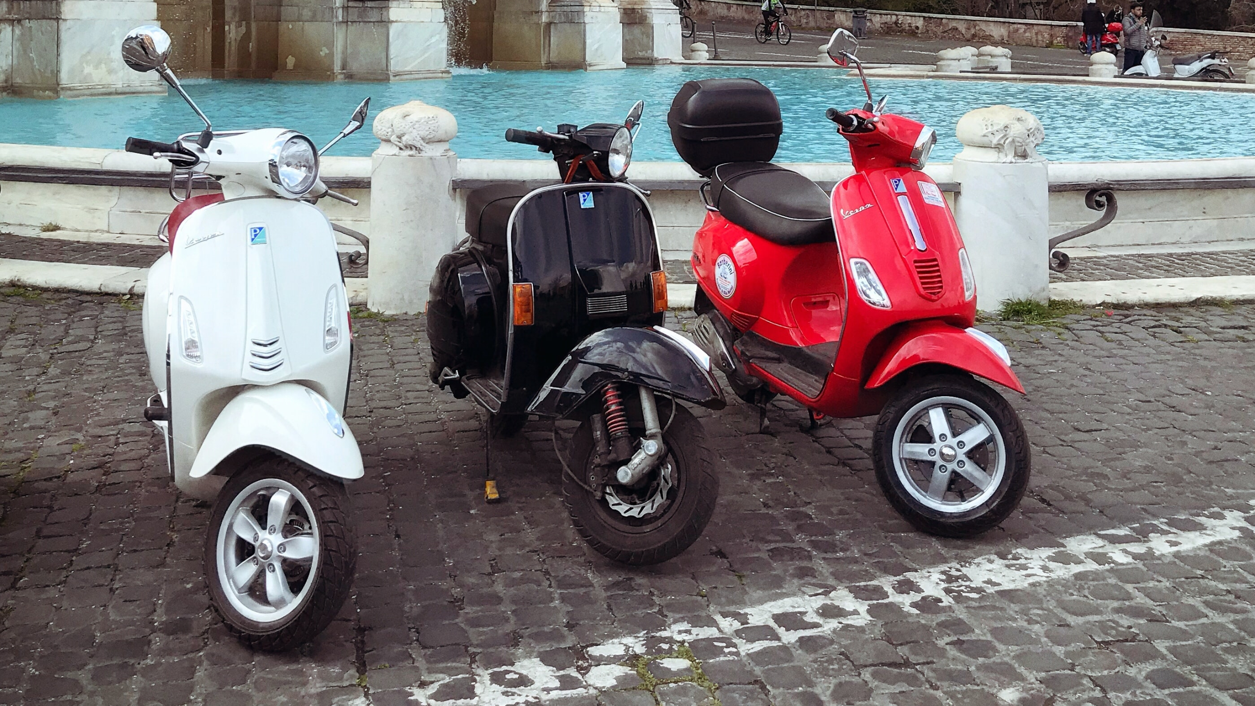 Three scooters lined up side by side in front of a fountain