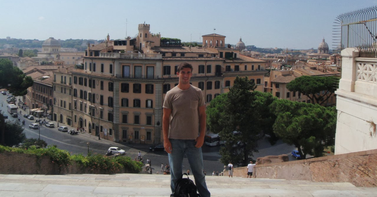Guy standing center frame on top of steps to Campidoglio