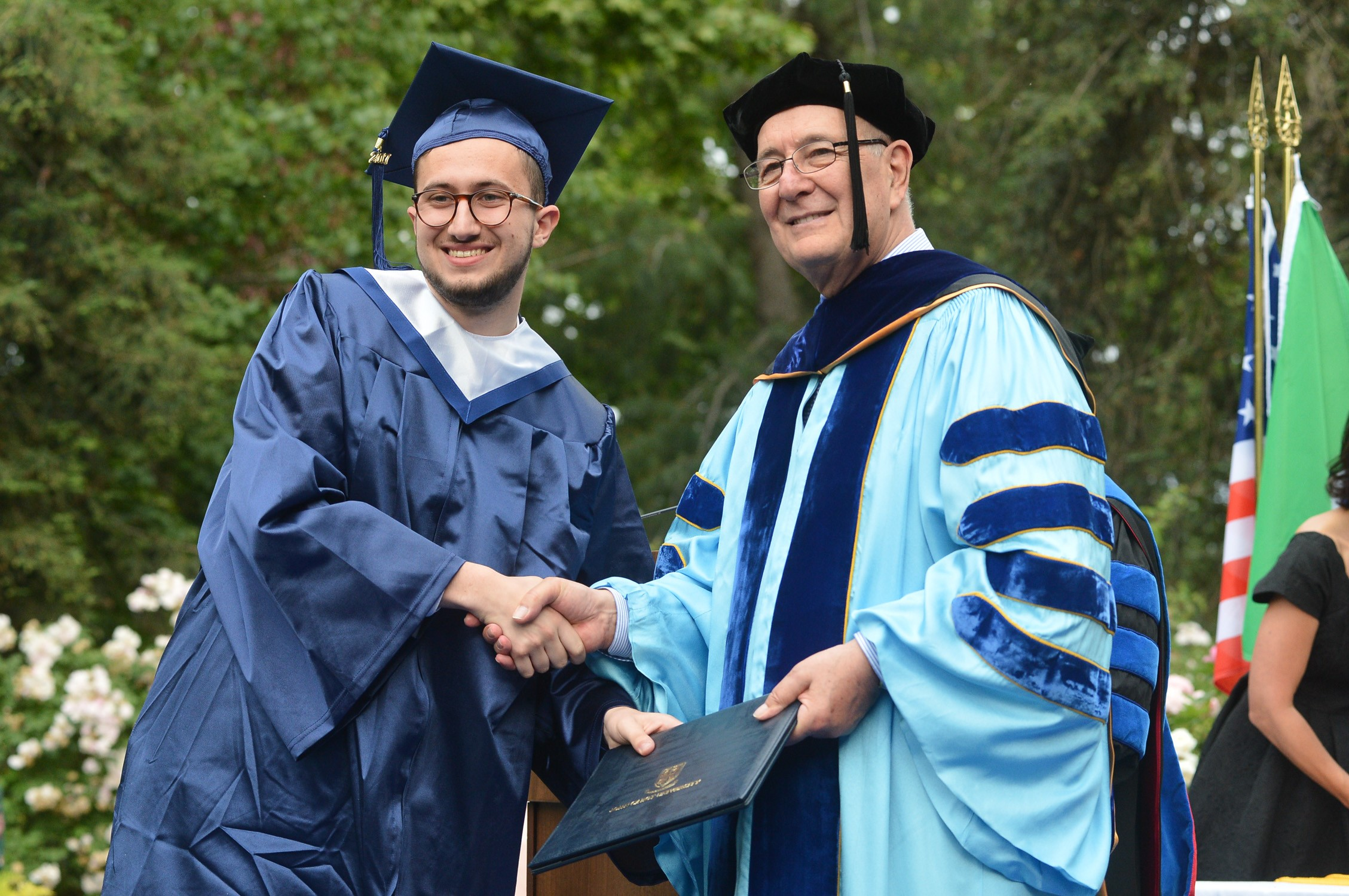 Student and President of the University shaking hands during the graduation ceremony. Both wearing blue caps and gowns